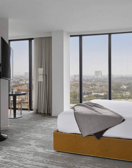 Corner room with king bed, floor to ceiling windows, flat screen TV mounted on a stand, and seating area