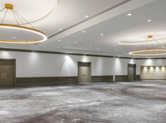 Empty Jordan ballroom with circular chandeliers and gray carpeted floor