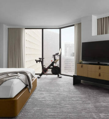 Large room with flat-screen tv on entertainment center, small sitting table and peloton bike