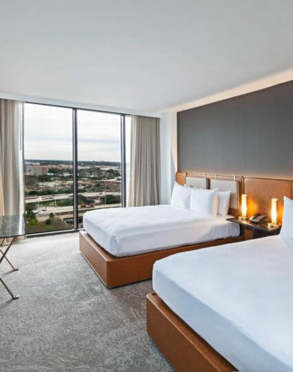 Double queen sized room with view of Houston through floor to ceiling windows