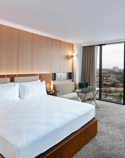 King sized bed room with seating area that includes view of Houston through floor to ceiling windows.