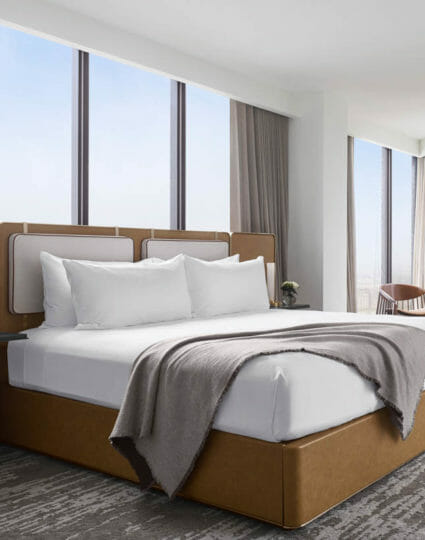 Luxurious king sized bed surrounded by floor to ceiling windows in the Presidential Suite