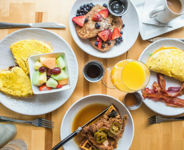 Top down view of four breakfast plates such as pancakes, omelette and bacon, french toast, and chicken and waffles