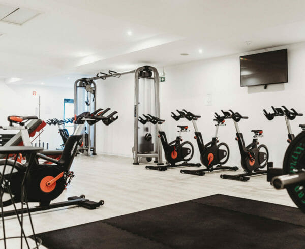 Several spinning bikes and various other fitness equipment in the fitness center