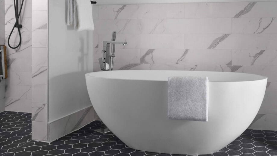White luxurious bathtub with towel draped over the side