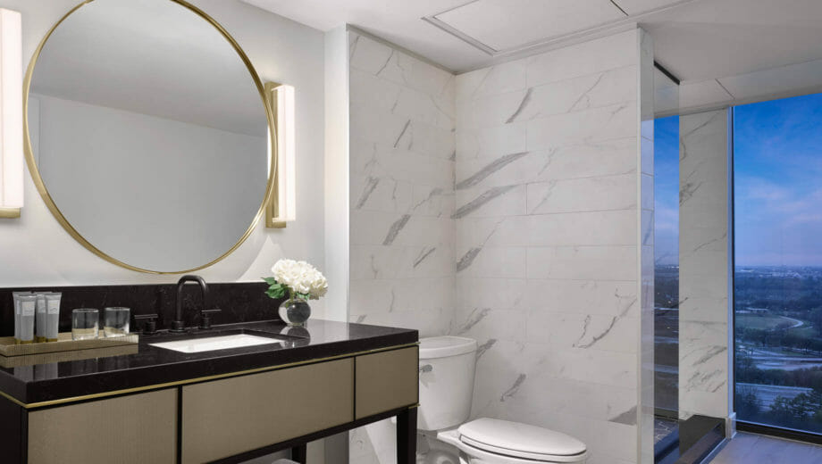 Bathroom vanity with gold framed circular mirror, marble wall tile, and entry to bathroom with floor to ceiling windows.