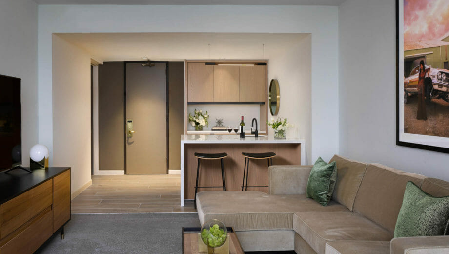 Suite kitchen area with sectional, bar area, and suite entry