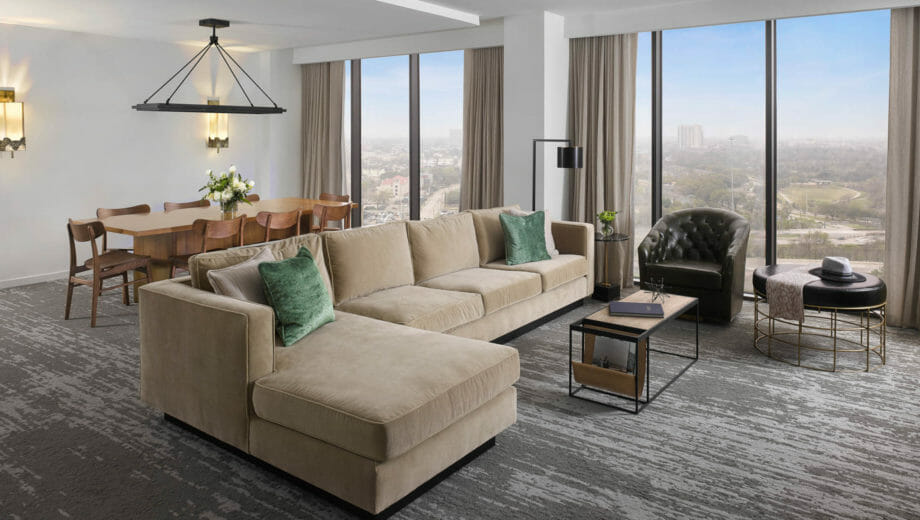 Spacious Presidential Suite living room with floor to ceiling windows, tan sectional in seating area and dining table behind it.