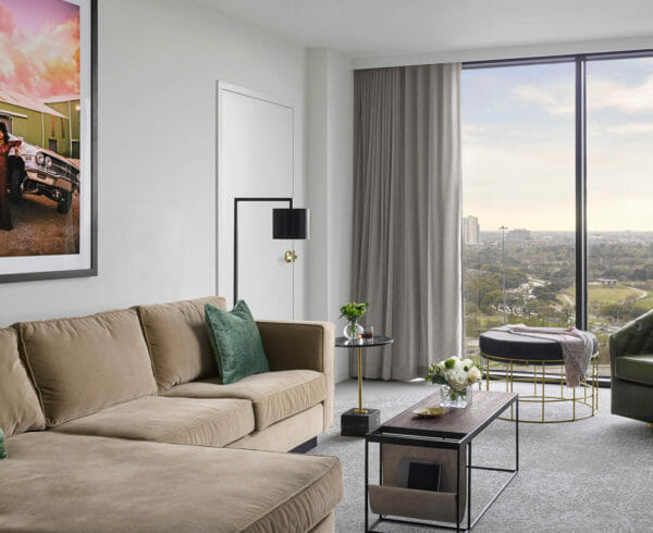 Suite living room area with tan sectional and lounge chair with modern lighting fixtures and coffee table