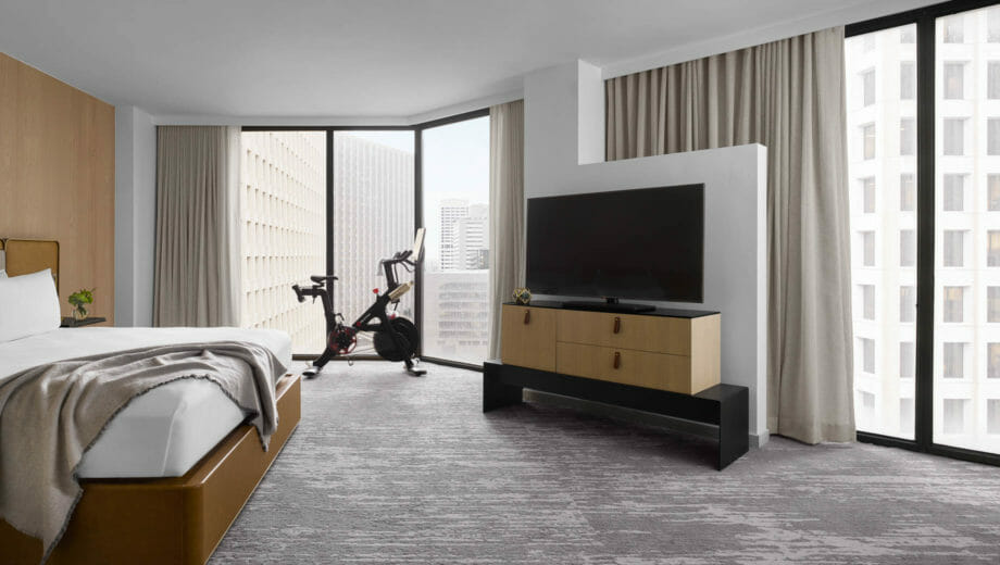 A king sized bed corner room with a TV and Peleton