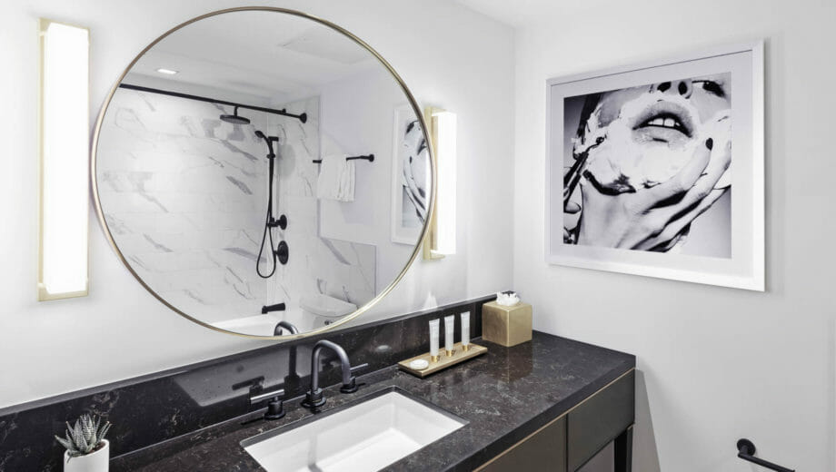 Circular mirror above bathroom sink with black counters
