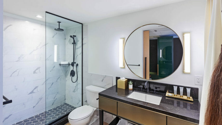 Bathroom with stand up shower, toilet, and vanity with circular mirror