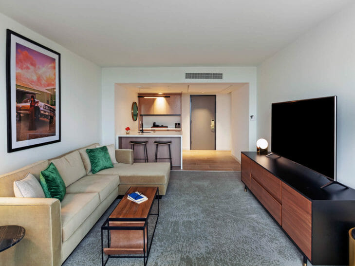 Living room with tan sectional, entertainment center with flatscreen tv, and kitchen area