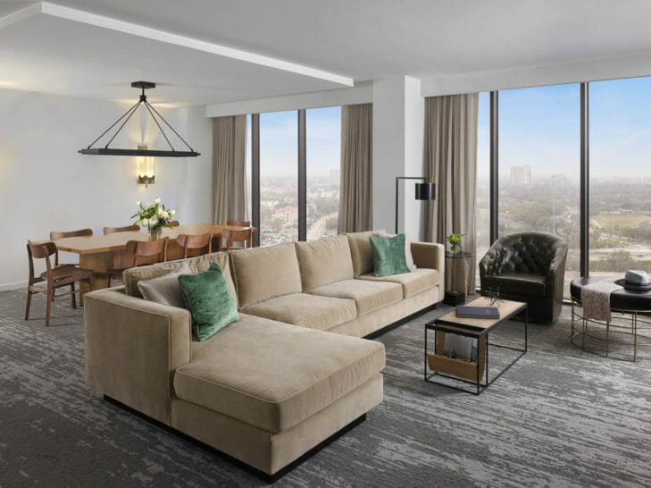 Living room area of Suite with tan sectional and dining table that seats eight people