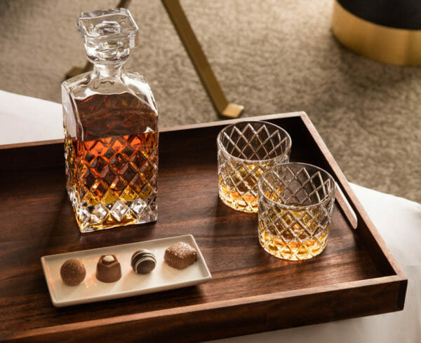 Whiskey decanter and glasses on bedside tray with chocolates