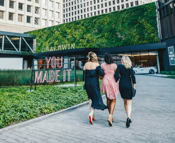 Three women walking towards C. Baldwin Hotel