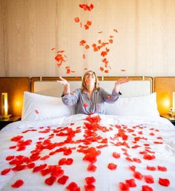A woman in bed throwing rose petals in the air.