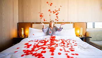 A woman in bed throwing rose petals into the air.
