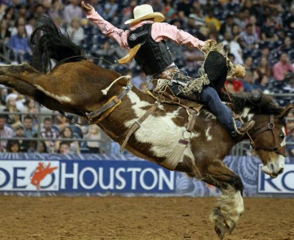 A cowboy on a horse bucking