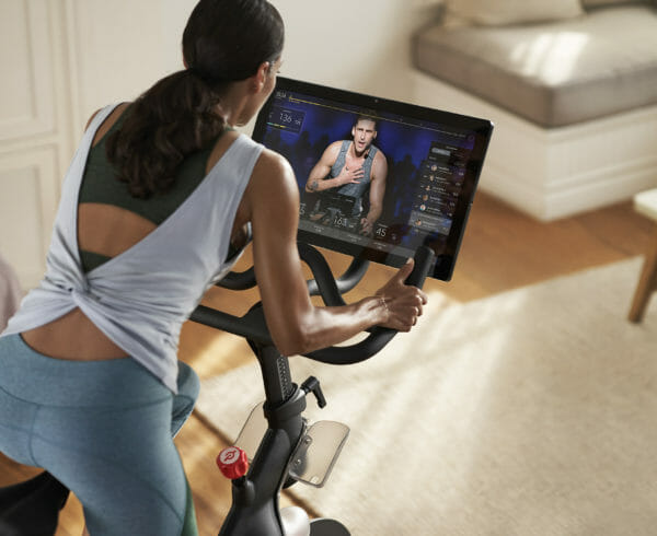 A woman on a peleton taking a class with an instructor on screen