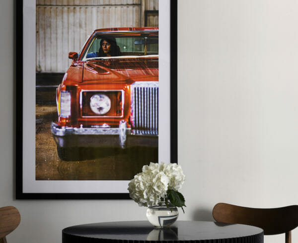 A close up of a dining room table with a picture of a woman in a red car on the wall