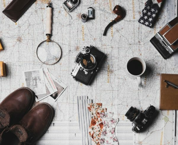 A map with knick knacks like cameras, spy glass, brown shoes and a pipe on top of it.